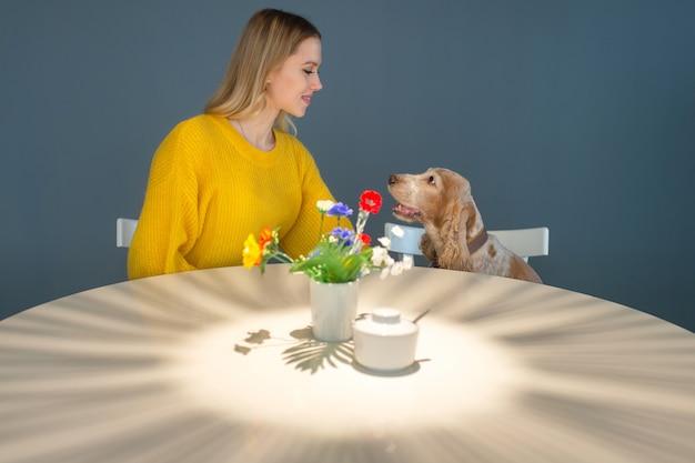 Vrolijke vrouw in gele blouse aan de tafel zitten en communiceren met haar mooie grappige cocker spaniel puppy
