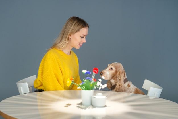 Vrolijke vrouw in gele blouse zittend in stoel in restaurant aan tafel en communiceren met haar mooie grappige cocker spaniel puppy
