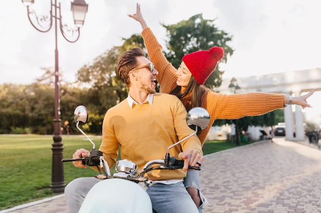 Vrolijke vrouw in grappige rode hoed genieten van extreme rit met vriendje