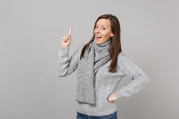 Vrolijke vrouw in grijze trui sjaal met wijsvinger omhoog met geweldig nieuw idee geïsoleerd op een grijze achtergrond. gezonde mode levensstijl mensen oprechte emoties koude seizoen concept. bespotten kopie ruimte.