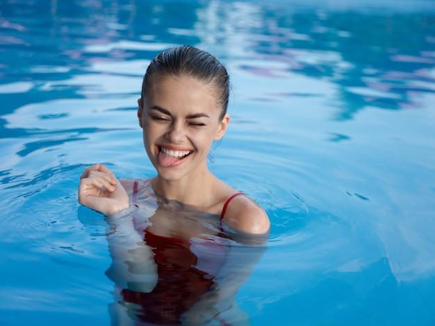 Vrolijke vrouw in het zwembad rode zwembroek vrije tijd luxe natuur