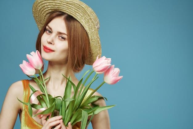 Vrolijke vrouw in hoed boeket bloemen elegantie luxe studio bijgesneden weergave. hoge kwaliteit foto
