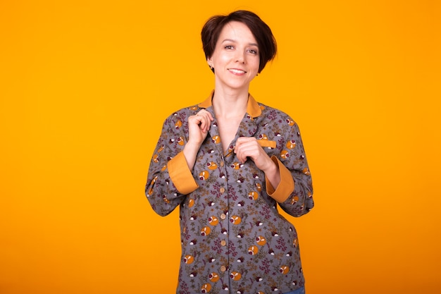 Vrolijke vrouw in huiskleding pyjama studio levensstijl gele achtergrond emoties. kopieer ruimte.