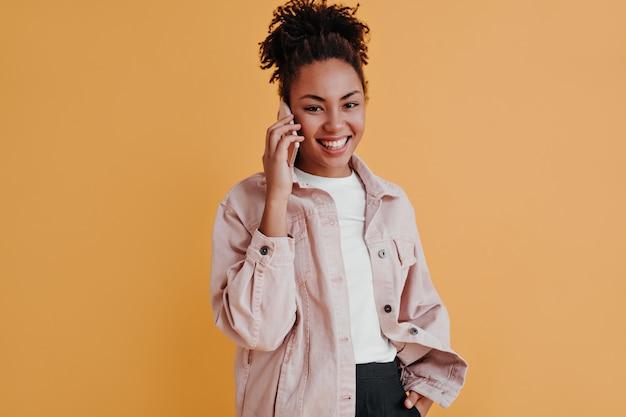 Vrolijke vrouw in jas praten over smartphone