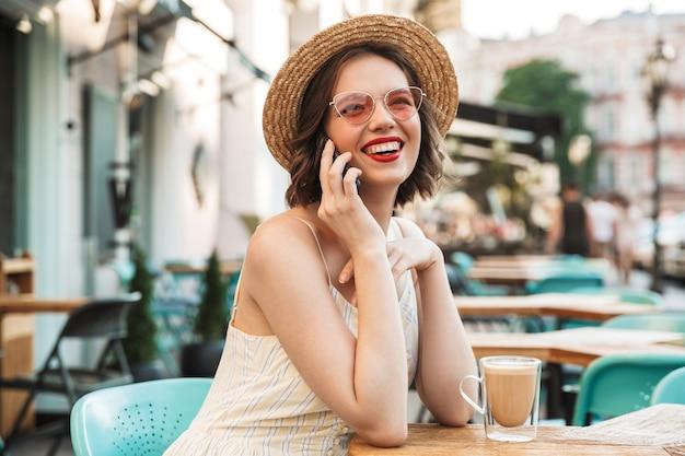 Vrolijke vrouw in jurk en strooien hoed praten door smartphone