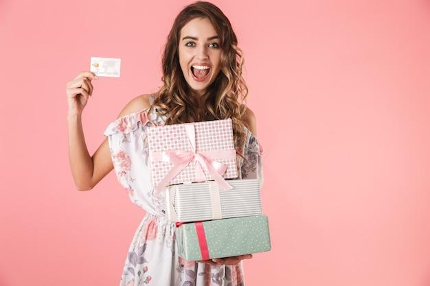 Vrolijke vrouw in jurk met creditcard en dozen met aankoop, geïsoleerd op roze