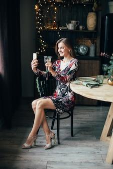 Vrolijke vrouw in kleurrijke jurk drinkt alcohol in de keuken en selfie doen