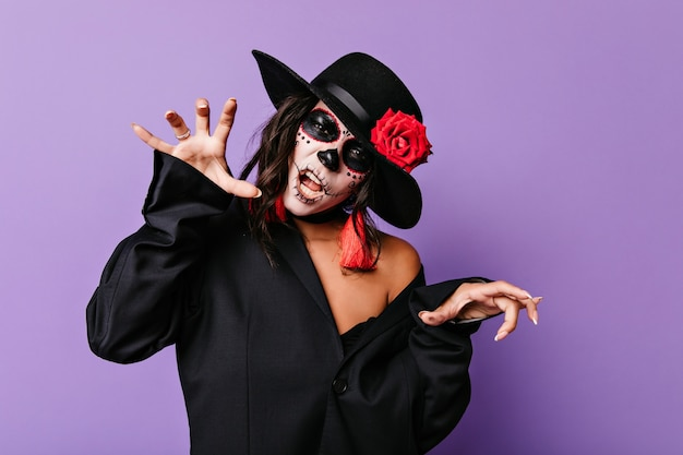 Vrolijke vrouw in muertos-kleding die pret heeft op feestje. geweldig vrouwelijk model met zombie schminken poseren in halloween.