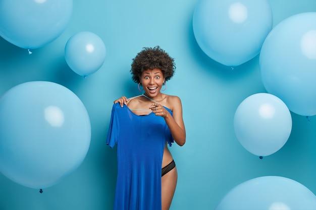 Vrolijke vrouw in ondergoed, kiest de beste outfit, bereidt zich voor op een belangrijke vergadering, houdt blauwe elegante jurk op hanger, wijst naar je en glimlacht breed, poseert tegen opgeblazen heliumballonnen