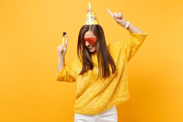Vrolijke vrouw in oranje grappige glazen verjaardagsfeestje hoed met spelen pijp stijgende handen wijsvingers omhoog, dansen vieren geïsoleerd op gele achtergrond. mensen oprechte emoties, levensstijl.