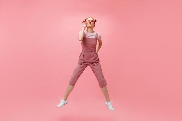 Vrolijke vrouw in overall en wit t-shirt zet zonnebril op en springt op roze achtergrond.