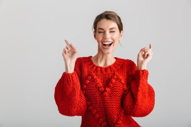Vrolijke vrouw in rode trui lachen en wijzende vingers naar boven geïsoleerd op witte achtergrond