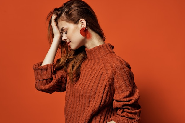 Vrolijke vrouw in rode trui oorbellen charme cosmetica model