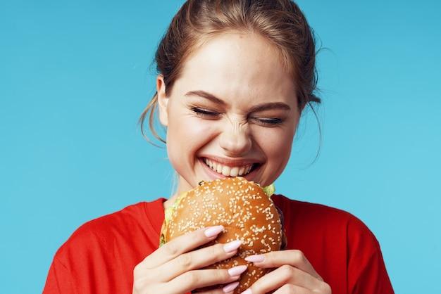 Vrolijke vrouw in rode tshirt hamburger in handen fastfood blauwe achtergrond