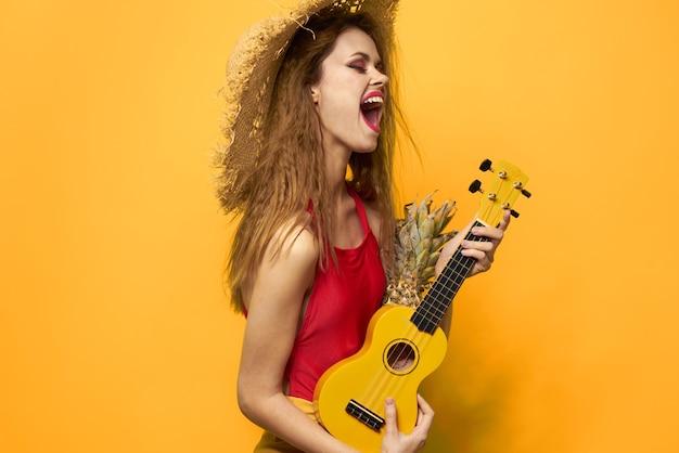 Vrolijke vrouw in rode ukelelet-shirt exotische fruit gele levensstijl