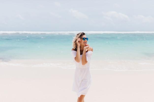 Vrolijke vrouw in romantische witte kledij staande op zee. extatische vrouw lachen in zonnebril zomerdag doorbrengen op oceaan.