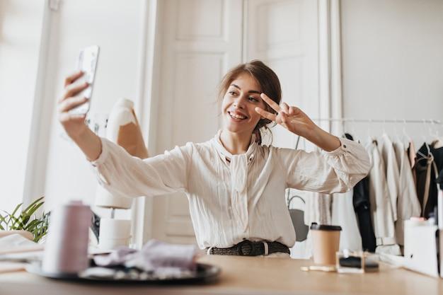 Vrolijke vrouw in stijlvolle blouse die selfie neemt en vredesteken toont