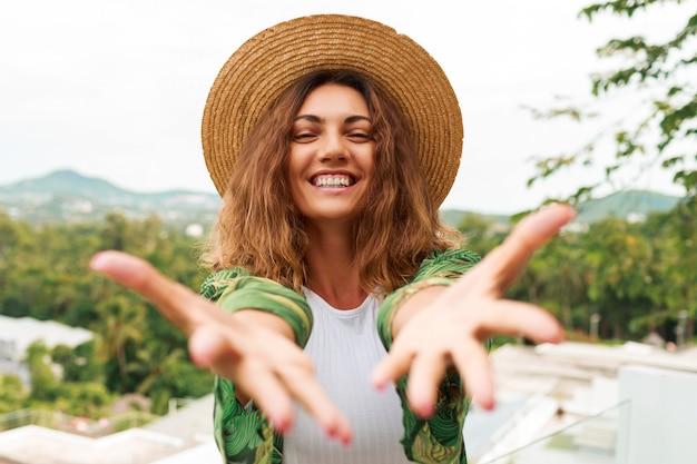 Vrolijke vrouw in stro hoed, met plezier, strekt de handen naar de camera.