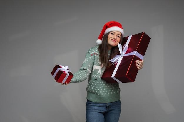 Vrolijke vrouw in trui en kerstmuts verheugt zich over dozen met haar kerstcadeautjes