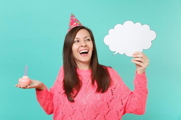 Vrolijke vrouw in verjaardagshoed opzoeken, taart met kaars vasthouden, lege blanco say cloud tekstballon voor promotionele inhoud geïsoleerd op blauwe achtergrond. mensen levensstijl concept. bespotten kopie ruimte.