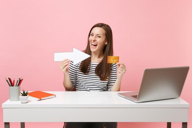 Vrolijke vrouw in vrijetijdskleding wijzend op creditcard met pijl zit op kantoor met moderne pc-laptop