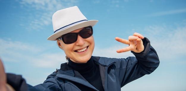 Vrolijke vrouw in witte hoed en zonnebril vormt tegen mooie blauwe hemel met wolken