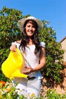 Vrolijke vrouw in witte jurk water geven bloemen met gele gieter