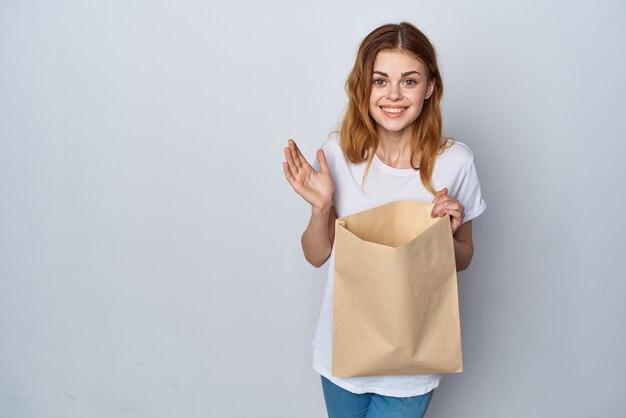 Vrolijke vrouw in witte t-shirt papieren boodschappentas