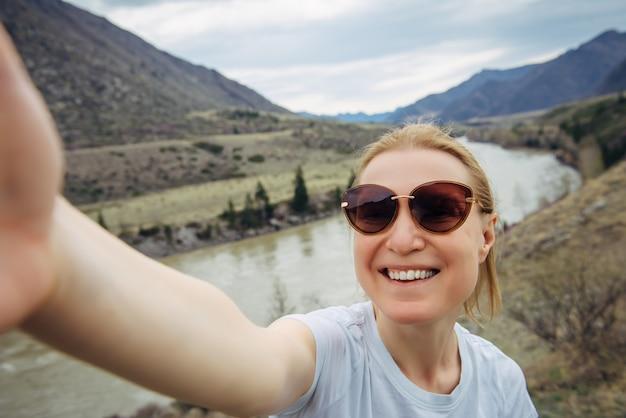 Vrolijke vrouw in zonnebril neemt een selfie op de achtergrond van het berglandschap. actieve levensstijl.