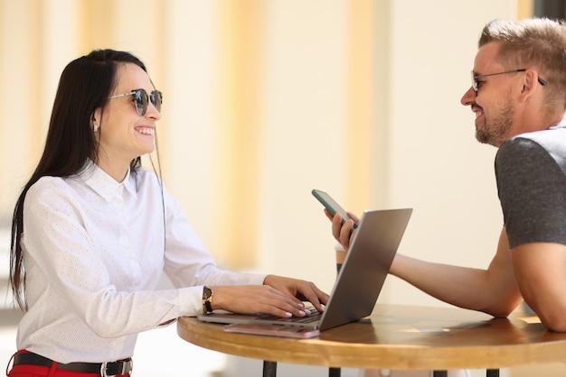 Vrolijke vrouw in zonnebril zitten aan ronde tafel in straat en typen op laptop. man ontmoet vrouw en neemt telefoonnummer.