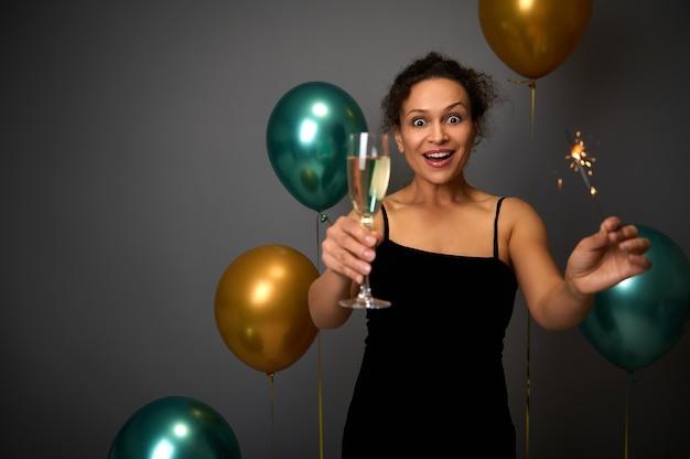 Vrolijke vrouw in zwarte avondjurk houdt een glas champagne en sterretjes vast, poseert tegen een grijze achtergrond met prachtige decoratie van gouden en groene luchtballonnen. kerstmis, verjaardagsconcept