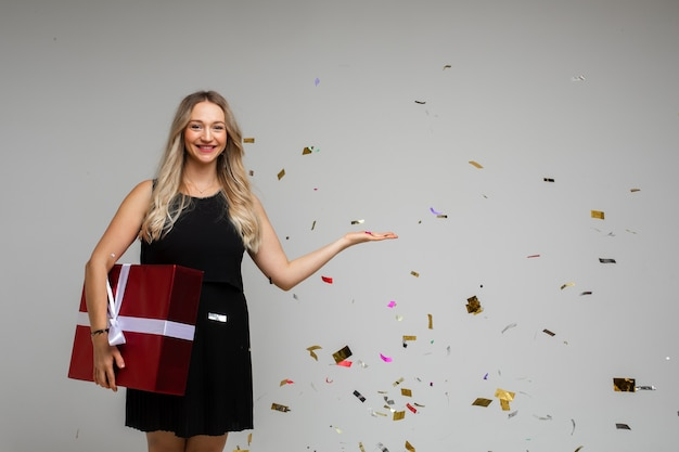 Vrolijke vrouw in zwarte jurk verheugt zich van doos met haar kerstcadeau met veel confetti om haar heen