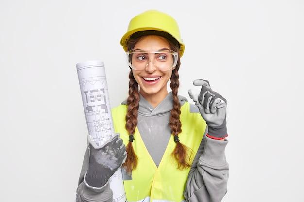 Vrolijke vrouw ingenieur hods bouwtekeningen gekleed in bouwer uniforme vormen klein handgebaar draagt beschermende veiligheidshelm handschoenen en bril inspecteert ontwerpen geïsoleerd over witte muur