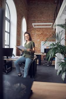 Vrolijke vrouw interieurontwerper of architect met een bril die naar de camera glimlacht terwijl hij aan het werk is