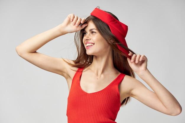 Vrolijke vrouw kijkt naar de zijkant van de handen bij het hoofd rode pet