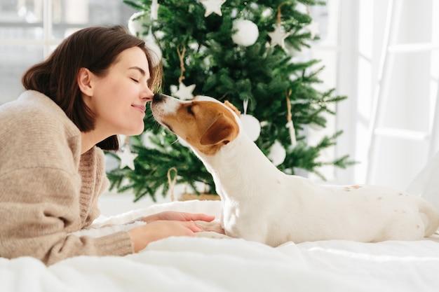 Vrolijke vrouw krijgt kus van favoriete hond, houdt ogen gesloten van plezier