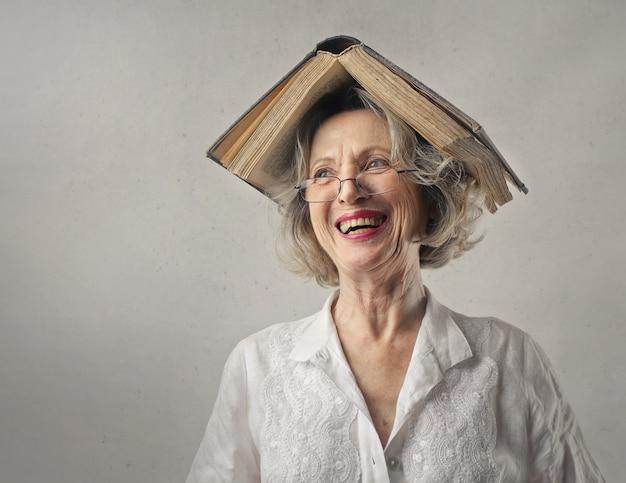 Vrolijke vrouw, lachend met een boek op haar hoofd