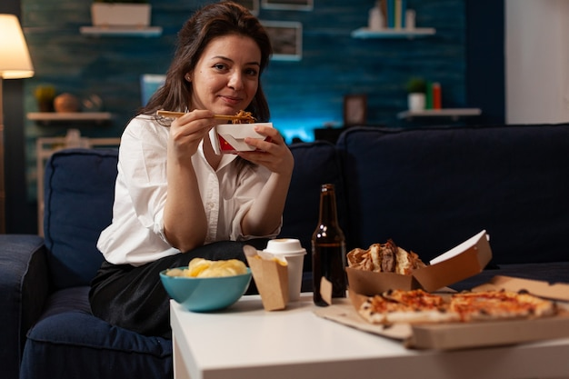 Vrolijke vrouw lekker chinees eten ontspannen op de bank