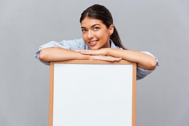 Vrolijke vrouw leunend op een leeg bord geïsoleerd op een grijze muur