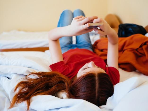 Vrolijke vrouw ligt thuis op het bed met de telefooncommunicatie