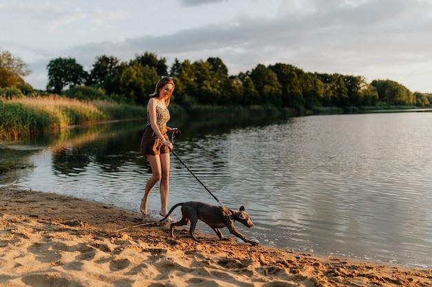 Vrolijke vrouw loopt met haar weimaraner-hond bij het meer