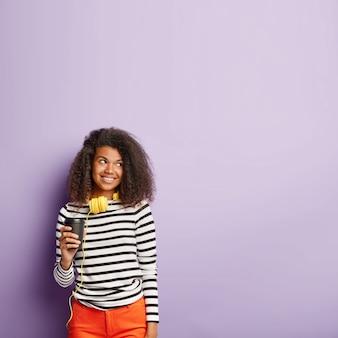 Vrolijke vrouw met afro kapsel drinkt afhaalmaaltijden koffie of thee