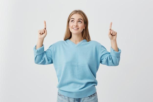 Vrolijke vrouw met blond haar, gekleed in blauwe trui en spijkerbroek, naar boven wijzend met haar vingers blij iets te zien. blond-haired meisje dat vreugdevol met tanden glimlacht