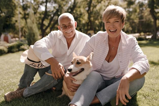 Vrolijke vrouw met blonde trendy kapsel in roze shirt en spijkerbroek lachen, corgi knuffelen en zitten met grijze harige man in brillen in park.