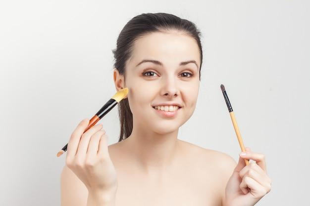 Vrolijke vrouw met blote schouders borstels in handen spons cosmetica