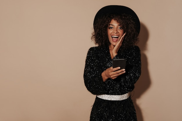 Vrolijke vrouw met brunette kapsel in trendy hoed en zwarte trui met glanzende riem die in de camera kijkt en smartphone op beige muur houdt..