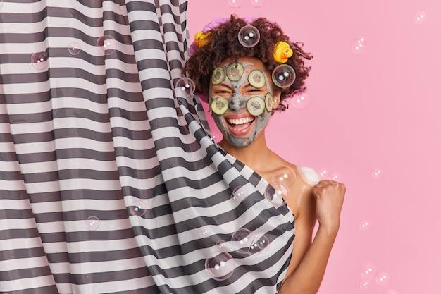 Vrolijke vrouw met donkere huid en afro-haar past kleimasker toe met plakjes komkommer, gebalde vuist glimlacht breed in goed humeur tijdens het douchen en ondergaat gezichtsbehandelingen poses binnenshuis