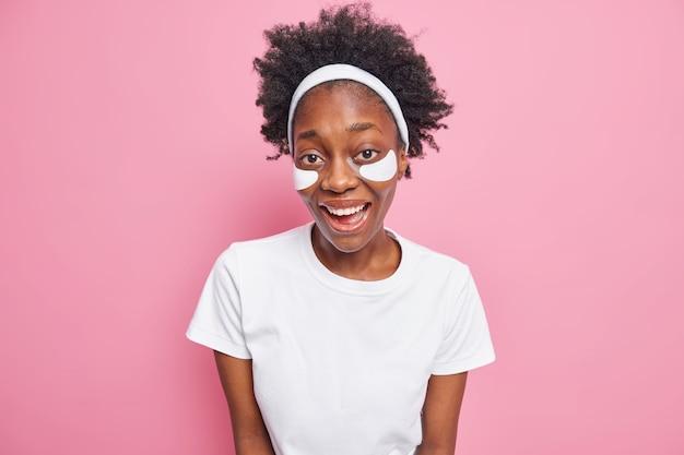 Vrolijke vrouw met donkere huidskleur en krullend haar heeft vlekken onder haar ogen