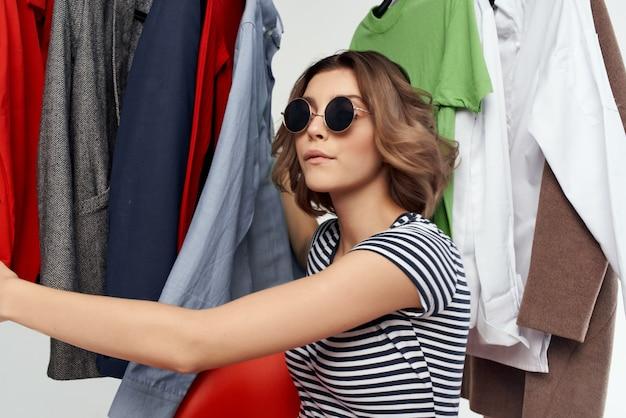 Vrolijke vrouw met een bril die kleding probeert winkel detailhandel geïsoleerde achtergrond