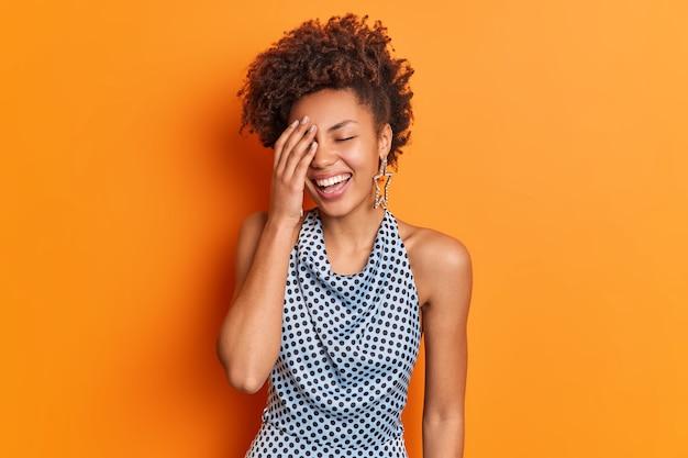 Vrolijke vrouw met een donkere huid maakt gezicht palm glimlacht aangenaam uitdrukt positieve emoties kan niet stoppen met lachen
